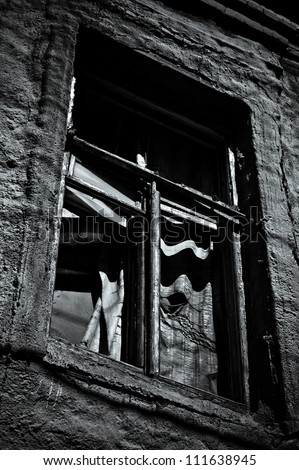 Window of abandoned house. Black and white photo in low key - stock photo
