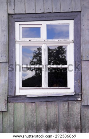 window of an old wooden house with the reflection of a tree in the glass
