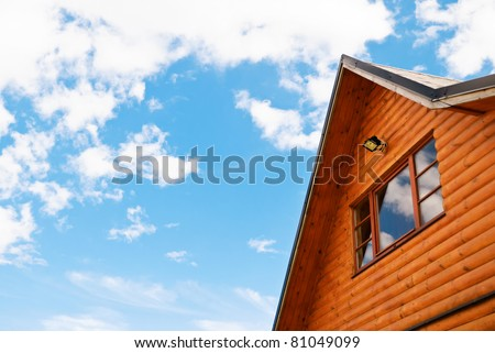 Window of mansard of the wooden house against the sky - stock photo