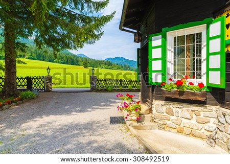 Window of typical alpine house decorated with flowers in summer season, Weissensee lake, Austria - stock photo
