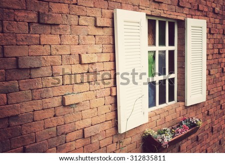 Window on a red brick wall with vintage tone - stock photo