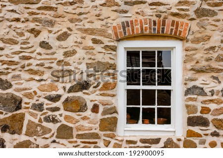 Window on stone wall at Old Salem Museum and Gardens. - stock photo