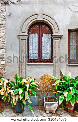 Window on the Facade of Italian House Decorated with Fresh Flower - stock photo
