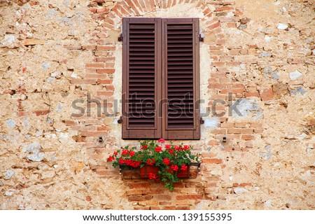 Window on the Facade of Italian stone wall - stock photo