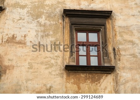 Window on the vintage grunge aged street wall of the old house with cracks - stock photo