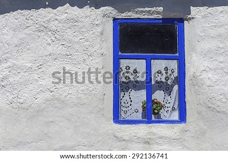 Window on the white wall of an old traditional peasant house - stock photo