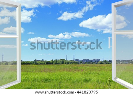window overlooking the summer landscape with field of grass and industrial objects far off. Green grass in the meadow and urban view far - stock photo