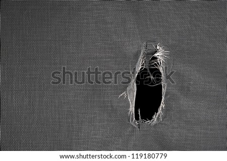 Window screen torn with a big hole against a black background. - stock photo