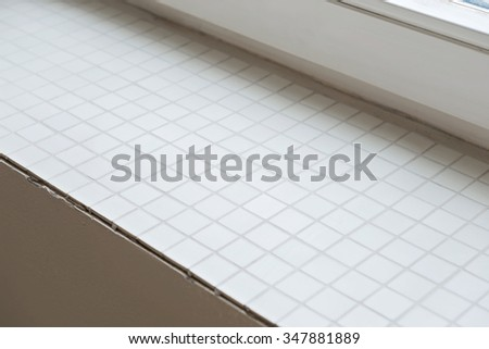 Window sill from mosaic tiles during renovation. Shallow depth of field. - stock photo
