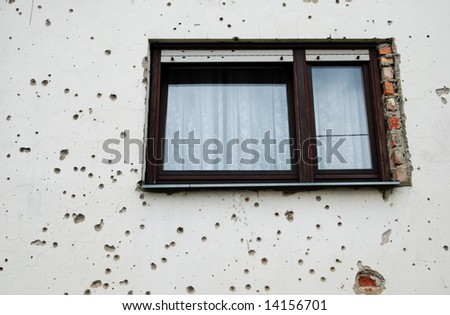 Window surrounded by bullet holes in a country still recovering from war
