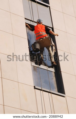 Window washer washing high office building windows hanging outside the building on ropes