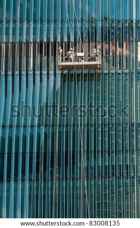 Window Washers  cleaning a complex all-glass facade of a modern building - stock photo