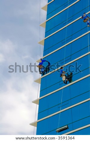 Window washers cleaning the exterior of a residential building - stock photo
