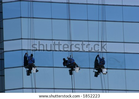 Window washers hanging from glass tower