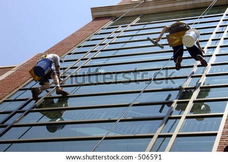 Window washers on side of building - stock photo