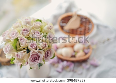 window wicker basket with eggs and a large bouquet of pink roses - stock photo