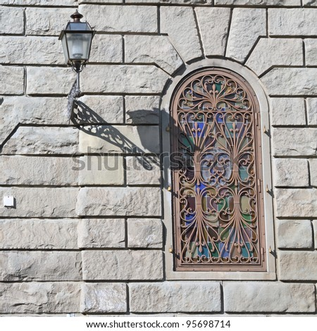 window with beautiful wrought iron and stained glass on monumental building in Florence, Tuscany, Italy, Europe - stock photo
