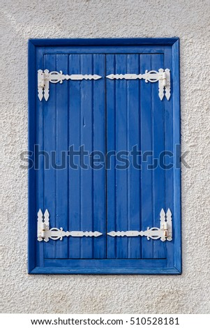 Window with blue shutters against a white wall, Greece