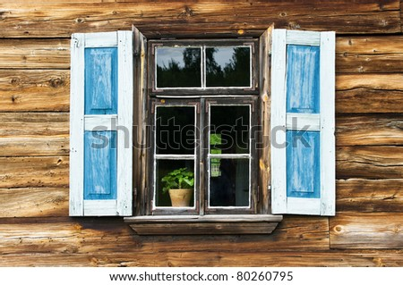 Window with blue shutters in old wooden wall - stock photo