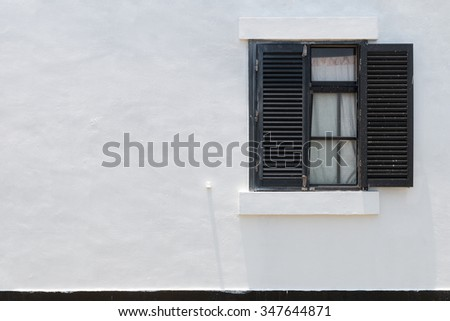 Window with brown blinds, one open and one closed, on a white wall showing the texture in the oblique sunlight