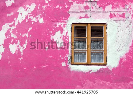 Window with brown frame on the background of the old pink stone wall
