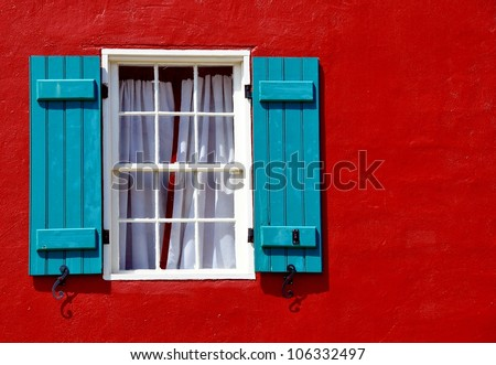 Window With Curtains And Blue Shutters On Red Stucco Exterior Wall