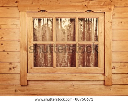 Window with curtains in the wooden wall