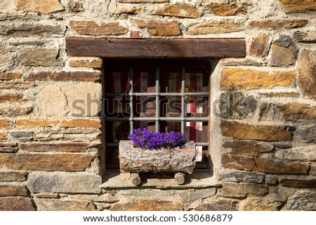 Window with flowers on the sill on a stone chalet