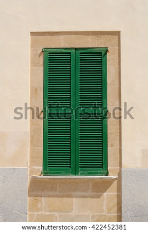 window with green closed shutter