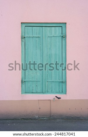 Window with green shutters closed, set in a pink plastered wall in Saint-Malo, France - stock photo