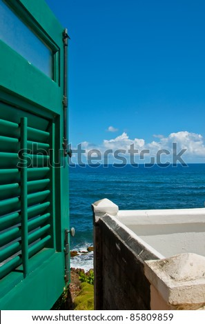 Window with green shutters overlooking the sea - stock photo