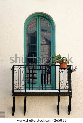 window with green trim and wrought iron railing on patio - stock photo