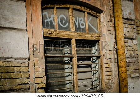 Window with metal frame and broken glass at old abandoned factory ruin plant building, with wall as background and copy space. - stock photo