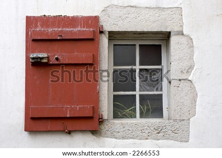 window with red shutter in white wall