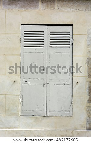 window with shutters on the limestone wall. Paris. France.