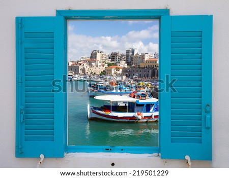 window with view of Heraklion old port with colorful boats, at sunny day, Crete, Greece - stock photo