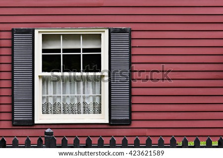 Window with white curtain and classic louvers on red wall - stock photo