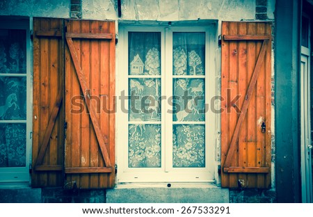 Window with white lace curtain decorated with galloping horses and wooden hinged shutters . (Amiens, Picardy, France)  Rustic background. Toned photo with vignette. - stock photo
