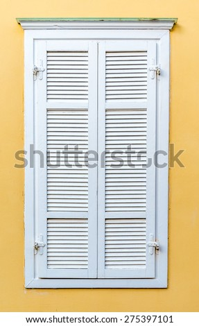 Window with white shutters on yellow wall - stock photo