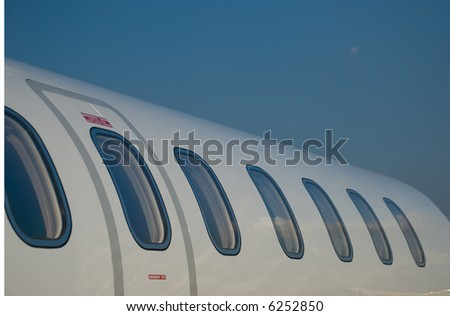 Windows and fuselage of a private jet - stock photo