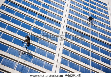 windows cleaners  working on boson's chair on high-rise building (skyscraper)