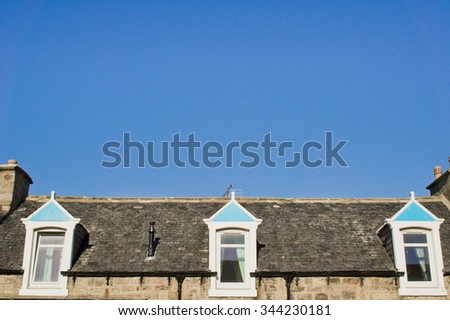 Windows of an attic room in a scottish house against a blue sky - stock photo
