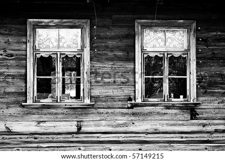 Windows of old, wooden cottage in the countryside in black and white - stock photo