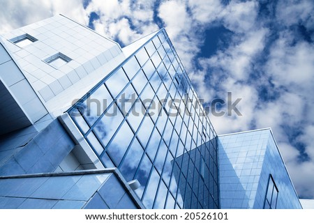 windows of skyscraper with reflections on a background cloudy sky - stock photo