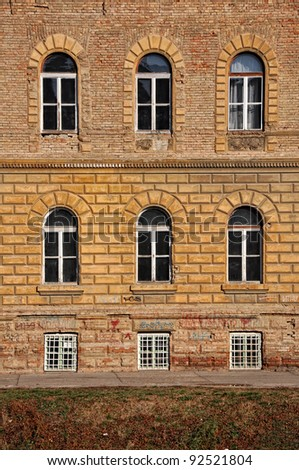 Windows on old yellow building - stock photo