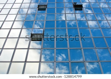 Windows on the office buildings with clouds reflecting