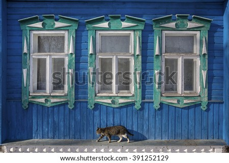 Windows with carved platbands on the blue old wooden house  - stock photo