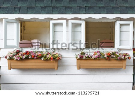 windows with flowers in hanging flower pots - stock photo
