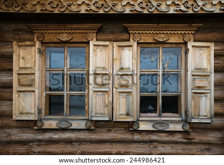 Windows with shutters, patterned on the wall of the old wooden house. - stock photo