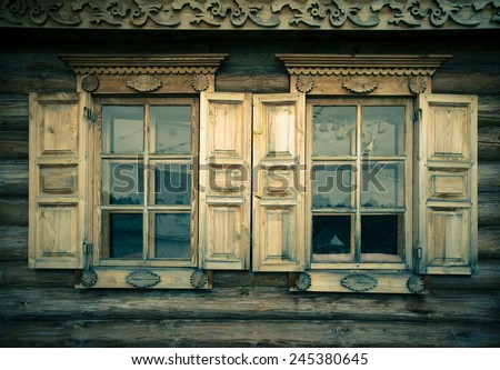 Windows with shutters, patterned on the wall of the old wooden house. Toned. - stock photo